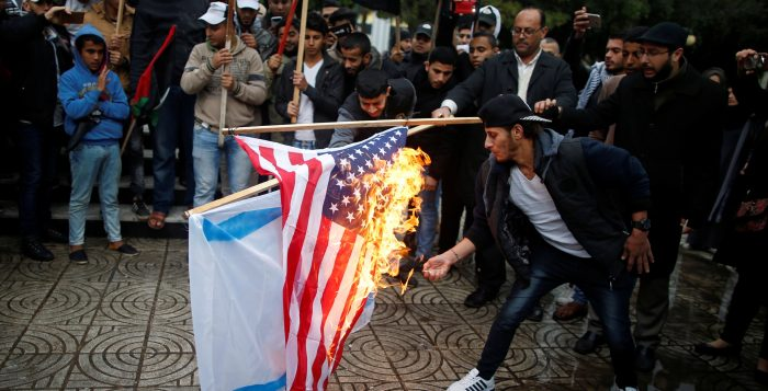 Palestinians burn an Israeli and a U.S. flag during a protest against the U.S. intention to move its embassy to Jerusalem and to recognize the city of Jerusalem as the capital of Israel, in Gaza City