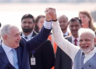Israeli Prime Minister Benjamin Netanyahu and his Indian counterpart Narendra Modi raise their arms upon Netanyahu's arrival at Air Force Station Palam in New Delhi