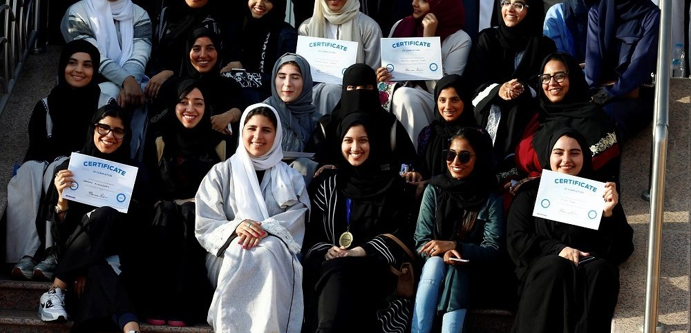 Women pose for a photo after attending a driving training at a university in Jeddah