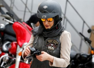 Maryam Ahmed Al-Moalem, a Saudi female bike rider, puts on her gloves during her lessons in advanced motorbike training at Harley Davidson training centre in Manama