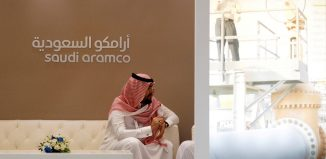 FILE PHOTO: A Saudi Aramco employee sits in the area of its stand at the Middle East Petrotech 2016 in Manama, Bahrain